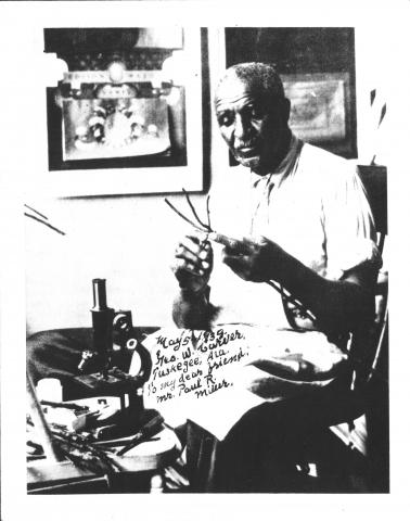 Photograph of Carver in his lab, autographed to Paul R. Miller, 1938.
