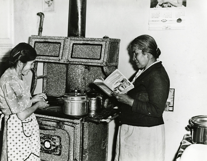 Black and white photograph of two women practicing canning next to the stove. One woman is holding a book.