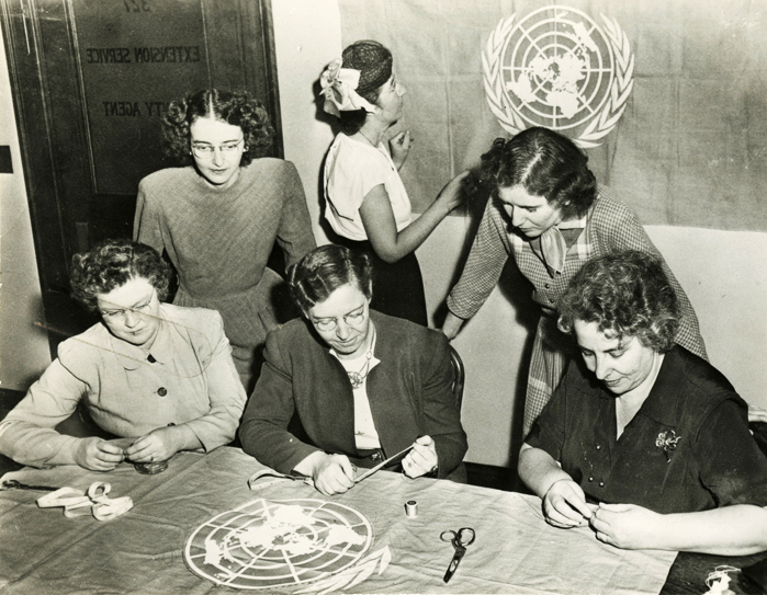 Black and white photograph of six female rural leaders training to conduct a United Nations flag meeting.
