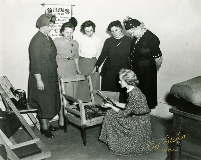 Black and white photograph of a specialist demonstrating spring tying to a few of the leaders during training school in Kosciusko County, Indiana, 1950.